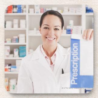 Pharmacist holding prescription in drug store drink coaster