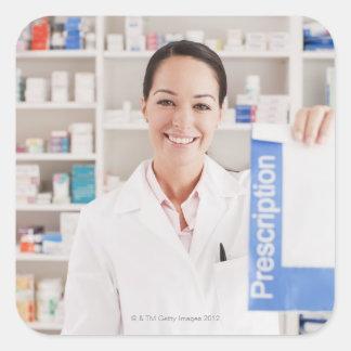 Pharmacist holding prescription in drug store square sticker