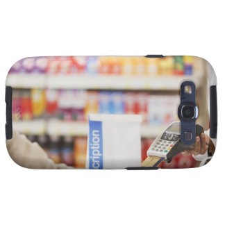Pharmacist holding security device for customer samsung galaxy SIII cases