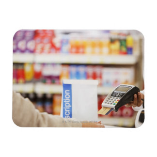 Pharmacist holding security device for customer magnet