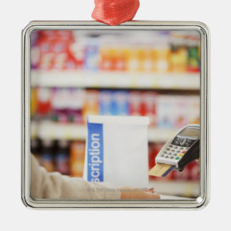Pharmacist holding security device for customer metal ornament