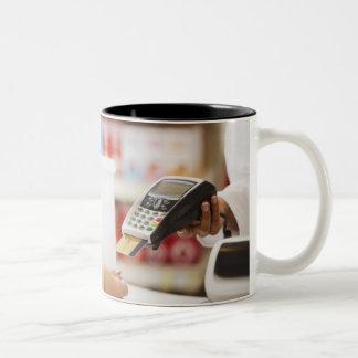 Pharmacist holding security device for customer Two-Tone coffee mug