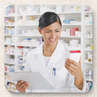 Pharmacist in drug store holding clipboard coaster