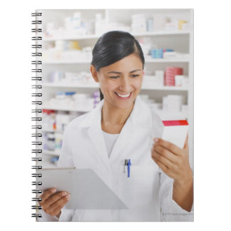 Pharmacist in drug store holding clipboard notebook