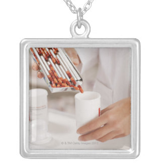 Pharmacist in drug store measuring pills into silver plated necklace