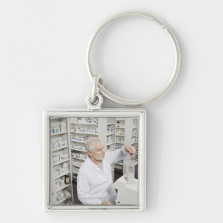 Pharmacist pouring pills into counting machine keychain