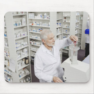 Pharmacist pouring pills into counting machine mouse pad