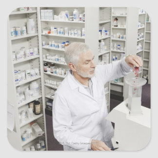 Pharmacist pouring pills into counting machine square sticker