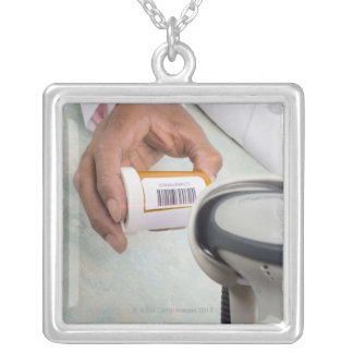 Pharmacist scanning pill bottle with a barcode silver plated necklace