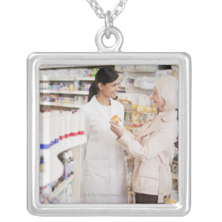 Pharmacist talking to customer in drug store silver plated necklace