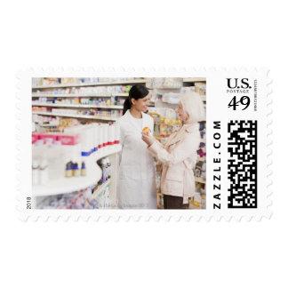 Pharmacist talking to customer in drug store stamp