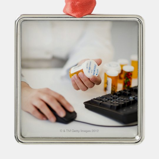 Pharmacist with pill bottles at computer metal ornament