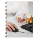 Pharmacist with pill bottles at computer note book