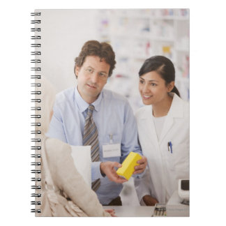 Pharmacists answering questions for customer in notebook