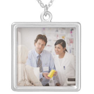 Pharmacists answering questions for customer in silver plated necklace