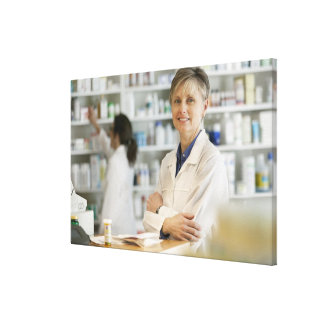 Pharmacists at counter of retail pharmacy canvas print