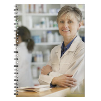 Pharmacists at counter of retail pharmacy notebook