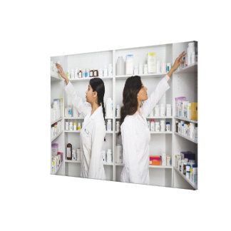 Pharmacists reaching for medication on shelves canvas print