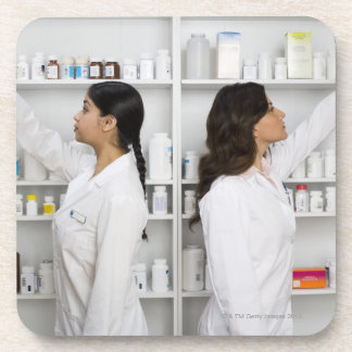 Pharmacists reaching for medication on shelves beverage coasters
