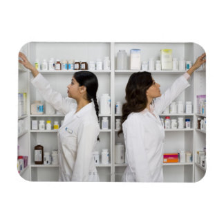 Pharmacists reaching for medication on shelves magnet