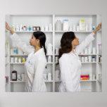 Pharmacists reaching for medication on shelves poster