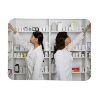 Pharmacists reaching for medication on shelves magnets