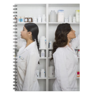 Pharmacists reaching for medication on shelves spiral notebook