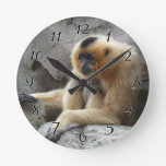 Photo of Orange and Black Gibbon Relaxing on Cliff Round Clock