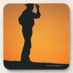 Photo, silhouette of a cowboy with his hand on drink coaster