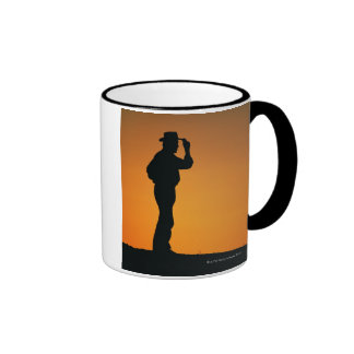 Photo, silhouette of a cowboy with his hand on ringer coffee mug