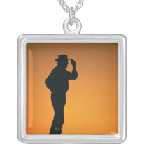Photo, silhouette of a cowboy with his hand on silver plated necklace