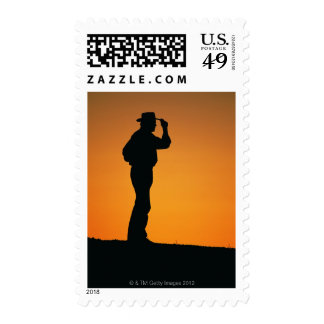 Photo, silhouette of a cowboy with his hand on stamps