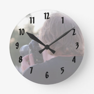 photographer taking picture male back of head round clock