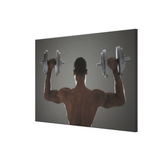 Physically fit man lifting dumbbells 2 canvas print