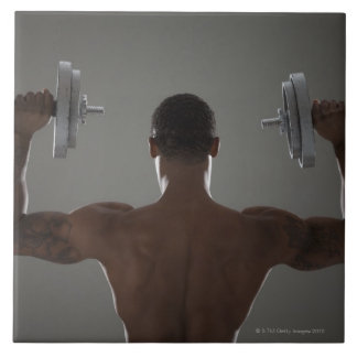 Physically fit man lifting dumbbells 2 tile