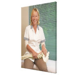 Physiotherapist with model of spine stretched canvas print