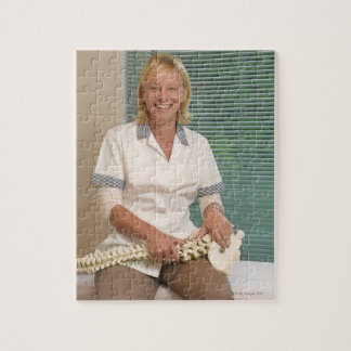 Physiotherapist with model of spine jigsaw puzzle