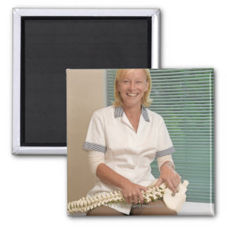 Physiotherapist with model of spine magnet