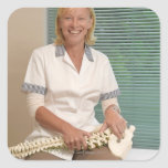 Physiotherapist with model of spine sticker