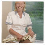 Physiotherapist with model of spine tile
