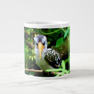 pico amarillo blanco negro del pájaro contra el ve taza grande