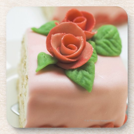 Piece of birthday cake with marzipan roses on beverage coaster
