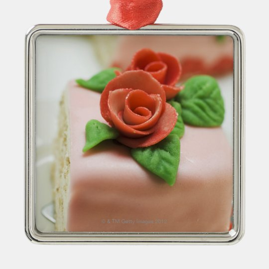 Piece of birthday cake with marzipan roses on metal ornament