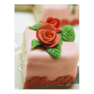 Piece of birthday cake with marzipan roses on postcard