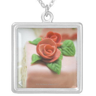 Piece of birthday cake with marzipan roses on silver plated necklace