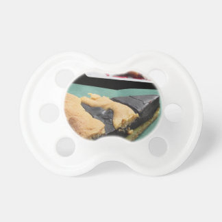 Piece of chocolate cake and cheesecake pacifier