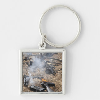 Pieces of enemy weapons lay out to cool off Silver-Colored square keychain