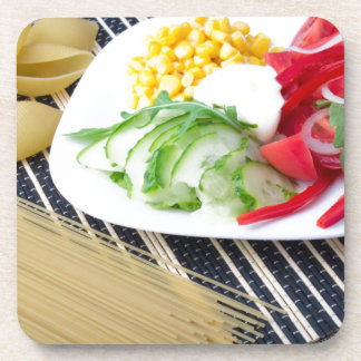Pieces of fresh raw vegetables on a white plate beverage coaster