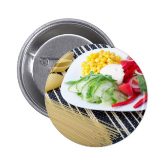 Pieces of fresh raw vegetables on a white plate button