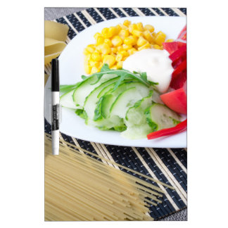 Pieces of fresh raw vegetables on a white plate dry erase board